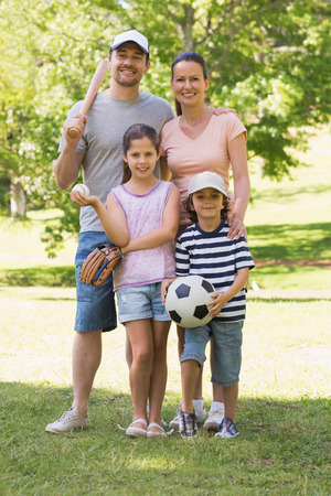 Full length portrait a family of four holding baseball bat and ball in the park photo