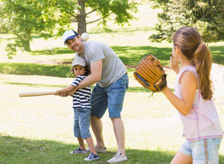 Family of three playing baseball in the park photo