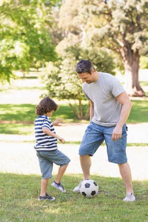 children playing: Full length of a father and son playing football in the park