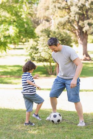 jugando: Integral de un padre y su hijo jugando al f�tbol en el parque