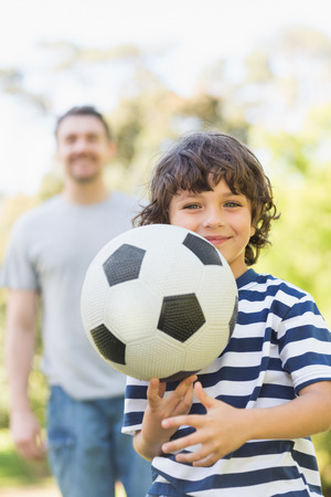 Portrait of a father and son playing football in the park photo