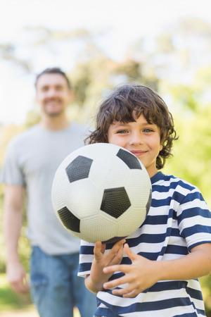 balones deportivos: Retrato de un padre y su hijo jugando al f�tbol en el parque