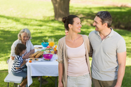 family dining: Couple with extended family dining background at outdoor table