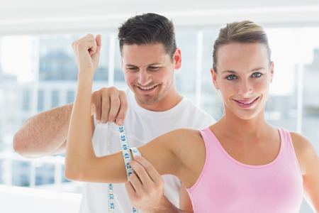 girth: Smiling young man measuring womans arm in bright exercise room