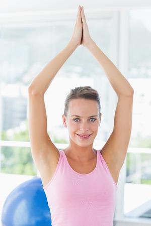 joined hands: Retrato de una mujer joven y sonriente con las manos juntas sobre la cabeza en un gimnasio brillante
