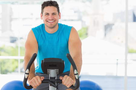 man working out: Retrato de un joven sonriente que se resuelve en la clase de spinning en el gimnasio
