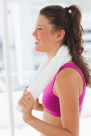Side view of a smiling fit young woman with towel standing in the gym
