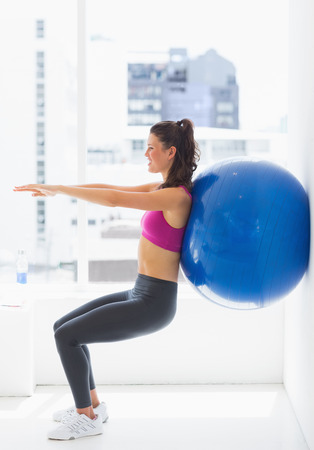 Side view of a fit young woman exercising with fitness ball at a gym photo