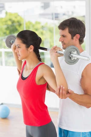 Male trainer helping young fit woman to lift the barbell in the gym photo