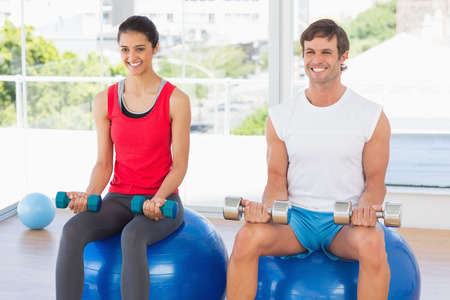 Happy man and woman lifting dumbbell weights while sitting on fitness balls in a bright gym photo