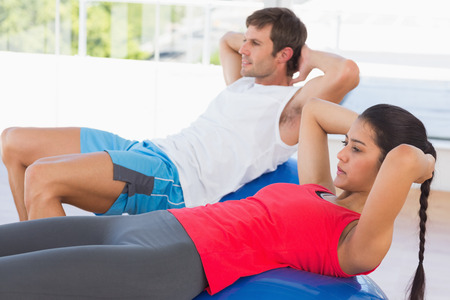 Side view of a fit young couple exercising on fitness balls in the bright gym photo