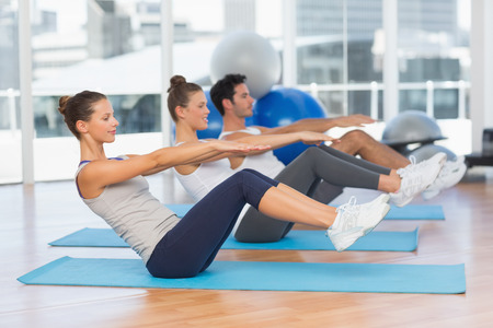 Side view of class stretching on mats at yoga class in fitness studio Stock Photo
