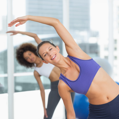 health club: Portrait of two sporty people stretching hands at yoga class in fitness studio Stock Photo
