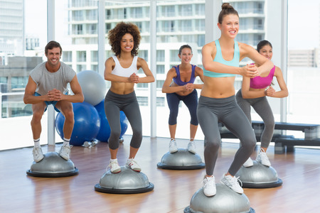 toning: Cheerful fitness class and instructor doing pilates exercise in bright room