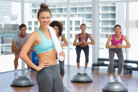 Portrait of a smiling woman with fit people performing step aerobics exercise in gymPortrait of a smiling woman with fit people performing step aerobics exercise in gym photo