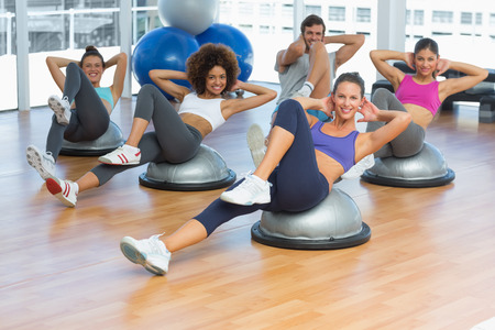 toning: Portrait of cheerful fitness class doing pilates exercise in bright room