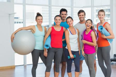 fitness: Retrato de los jóvenes en forma sonriente en una sala de ejercicio brillante