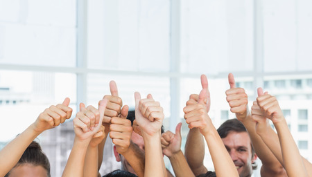 working out: Closeup of cropped people gesturing thumbs up in a bright exercise room Stock Photo