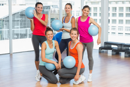 Portrait of happy fit young people with balls in a bright exercise room photo