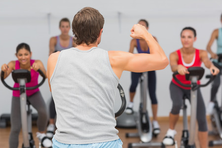 Male trainer and fitness class at spinning class in gym photo