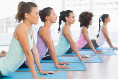 Zijaanzicht van een fit klas doet de cobra poseren in een lichte fitness-studio