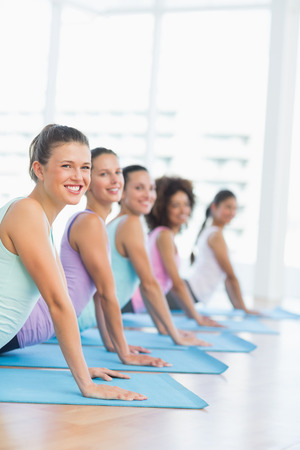 Side view portrait of a fit class doing the cobra pose in a bright fitness studio photo