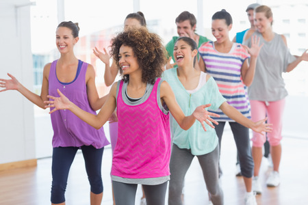body toning: Portrait of cheerful fitness class and instructor doing pilates exercise in bright room Stock Photo