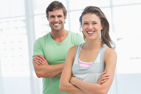 Portrait of a fit young couple standing with arms crossed in bright exercise room photo