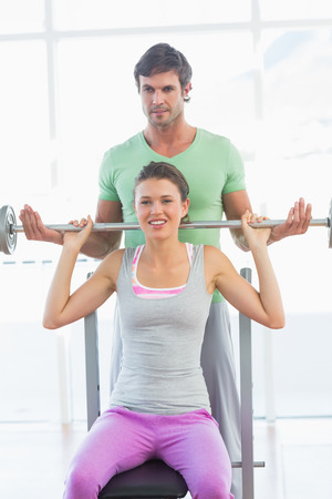 Male trainer helping young fit woman to lift the barbell bench press in the gym photo