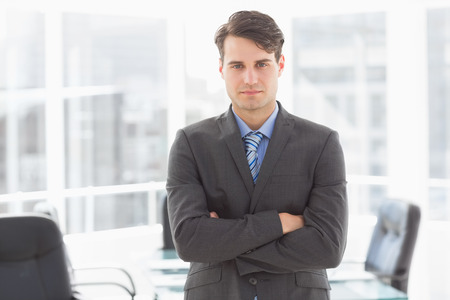 unsmiling: Handsome businessman leaning on board room table in the office