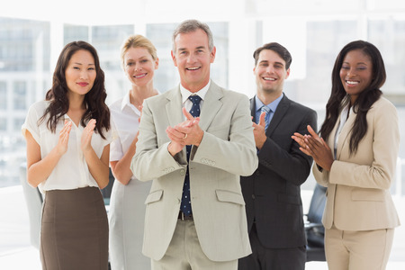 Business team standing and clapping at the camera in the office photo