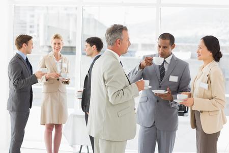 personas reunidas: La gente de negocios charlando y bebiendo caf� en una conferencia en la oficina