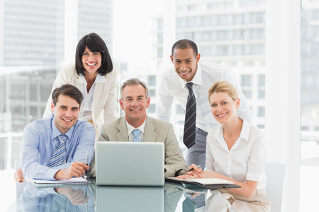 young business people: Happy business people gathered around laptop looking at camera in the office