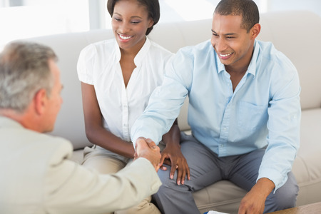Young couple shaking hands with salesman on the sofa in the office photo