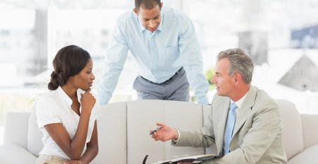 deal in: Salesman showing clients where to sign the deal in the office