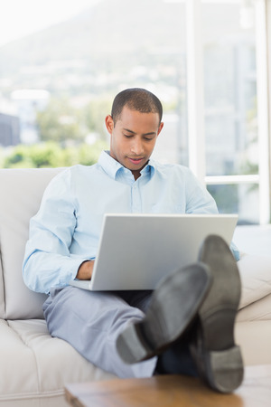 Businessman using laptop with his feet up in the office photo