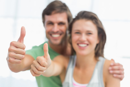 Portrait of a fit young couple gesturing thumbs up in bright exercise room Stock Photo