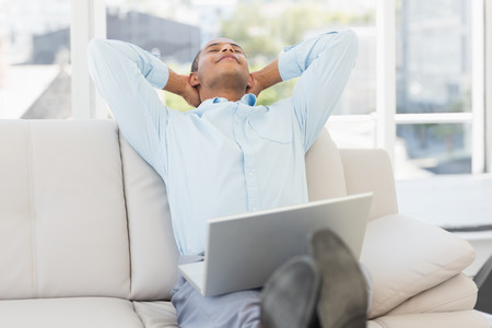 Relaxed businessman on the couch with laptop in the office photo