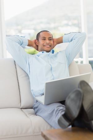 Relaxed smiling businessman on the couch with laptop in the office photo