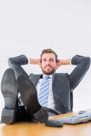 Full length of a relaxed young businessman sitting with legs on desk at office photo
