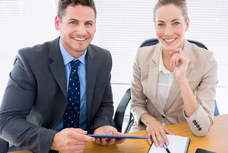 Portrait of a smartly dressed young man and woman in a business meeting at office desk photo