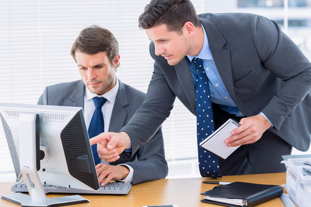 smartly: Smartly dressed young businessmen using computer at office desk