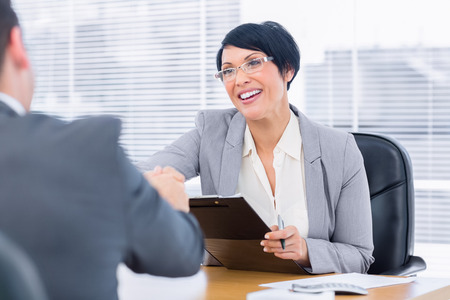 corporate meeting: Smartly dressed executives shaking hands after a business meeting in the office