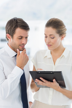 Smartly dressed young man and woman using digital tablet in a bright office photo