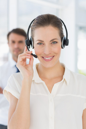 Close-up of a beautiful female executive with headset in a bright office photo