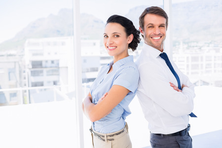 Portrait of a smiling young business couple standing with arms crossed in a bright office photo