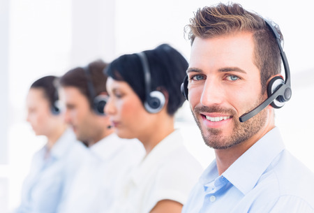 call centre: Side view of a group of business colleagues with headsets in a row at office Stock Photo