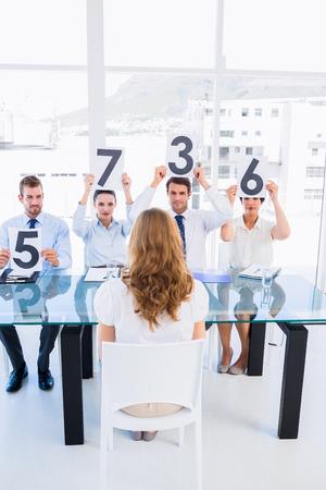comit� d entreprise: Groupe de juges du panel tenant des signes de pointage en face d'une femme au bureau lumineux
