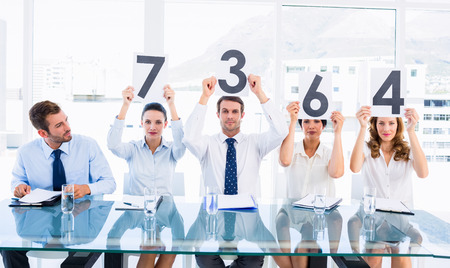 Portrait of a group of panel judges holding score signs in a bright office photo