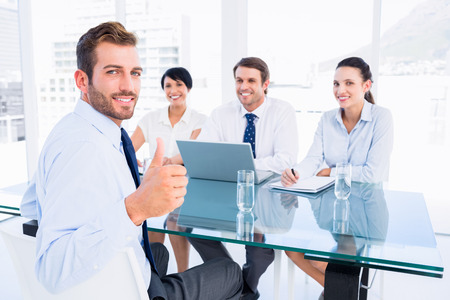 JOB INTERVIEW: Portrait of an executive gesturing thumbs up with recruiters during a job interview at office Stock Photo